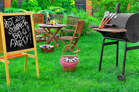 lawn party: An Invitation To A Summer Barbecue Grill Party 2016, Written on Blackboard, Barbecue Charcoal Grill Appliance And Outdoor Wooden Furniture On The Backyard Lawn In The Background Stock Photo
