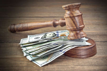 antitrust: Judges or Auctioneers Gavel Or Hammer And Big Money Stack On Wooden Bench Or Wooden Table Background, Concept For Financial Crime, Close Up