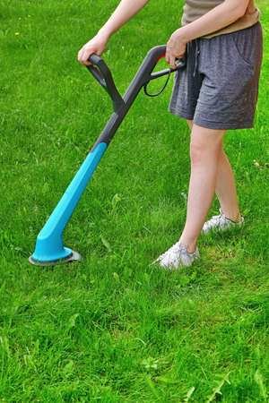corded: Young White Woman Holding  A Corded Grass Trimmer On The Backyard Lawn At Summertime