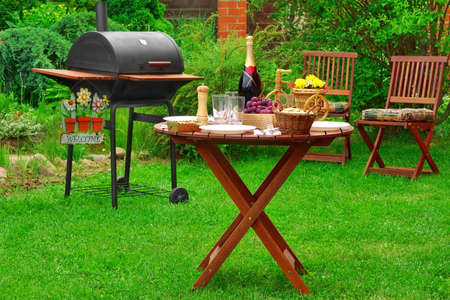 lawn party: Weekend BBQ Family Party Scene On The Backyard In Summertime. Charcoal Barbecue Grill Appliance With Welcome Sign And Outdoor Wooden Furniture  On The Garden Lawn. lunch Table With Food And  Beverage Stock Photo