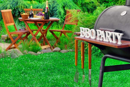 lawn party: Close-up Of Barbecue Charcoal Grill Appliance With Tools And BBQ Party Sign, Wooden Table With Food And  Beverages On The Backyard Lawn In The Blurred Background