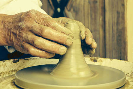 Close Up Of  Mature Potter Hands , Creating An Clay Pot On The Wheel, Toned Image