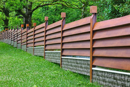 Modern Fence Made From Metal Siding And  Profile Sheet Like As Natural Wood Board Stock Photo