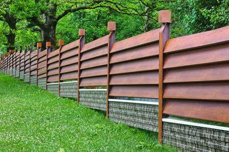 rusty: Valla moderno hecho de metal revestimiento y perfil del estudiante Como medida Junta de madera natural Foto de archivo