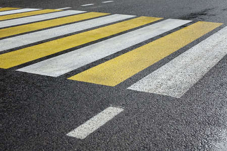 pedestrian crossing: Modern White Yellow Zebra Pedestrian Crossing On The Wet Black Asphalt Road In The perspective View, Background Or Texture Stock Photo