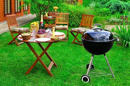 Escena del verano partido de la familia barbacoa en el jardín decorativo en el patio trasero. Parrilla de carbón Appliance, sillas de madera y una mesa con aperitivos y vinos de Champagne On The Fresh Césped