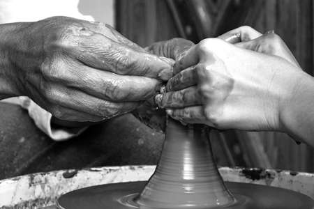 working hands: Close Up Of Mature Potter Hands Which Guide And Help Young Woman Make A Clay Pot On The Potters Wheel, Master Class Or Teamwork Concept