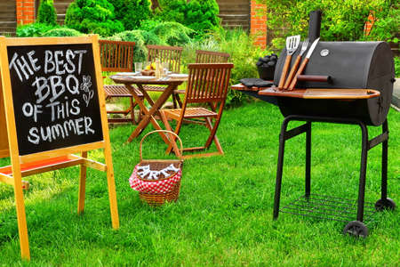 An Invitation To A Summer Barbecue Grill Party, Written on Blackboard, Barbecue Charcoal Grill Appliance And Outdoor Wooden Furniture On The Backyard Garden Lawn In The Background