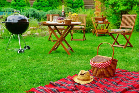 Closeup Of Red Picnic Blanket With Straw Hat And Basket Or Hamper. Blurred Outdoor Wooden Furniture In The Background. Family Home Backyard BBQ Party Or Picnic Conceptual Scene