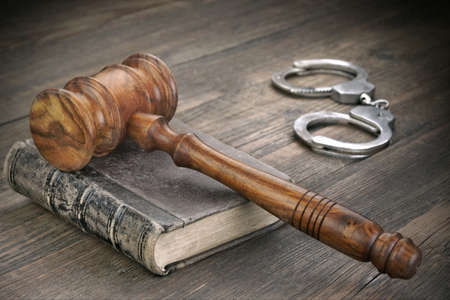 metal handcuffs: Judges Gavel Or Hammer, Silver Metal Handcuffs and Old Vintage Law Book On Wooden Table In The Courtroom, Law Concept, Close Up