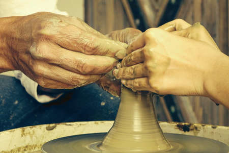 potters wheel: Close Up Of Mature Potter Hands Which Guide And Help Young Woman Make A Clay Pot On The Potters Wheel, Master Class Or Teamwork Concept