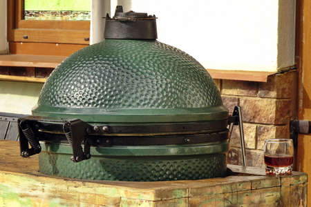 Closeup Of Green Ceramic BBQ Grill Mounted In The Table Referred To As A Kamado  Or  Mushikamado, Japanes Cooker Stock Photo