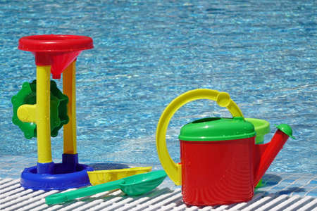 plastic scoop: Large Group Of Wet Beach Plastic Child Toys At The Poolside Near Water Surface. Colorful Watering Can, Water Mill, Bucket, Scoop, Shovel, Molds