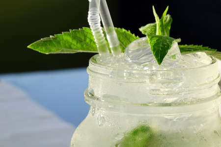 Close Up Of Misted Glass Mason Jar With Mojito Cocktail On The Table, Popular Summer Drink, Mixed With Rum, Soda Water, Cracked Ice,  Lime Wedges And Mint Sprig Stock Photo