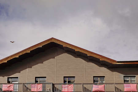 posted: Wooden Country House Mansard Balcony With Posted American Flags And Cloudy Sky