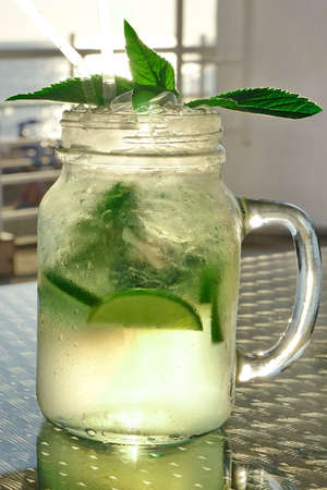 misted: Close Up Of Misted Glass Mason Jar With Mojito Cocktail On The Table, Popular Summer Drink, Mixed With Rum, Soda Water, Cracked Ice,  Lime Wedges And Mint Sprig Stock Photo