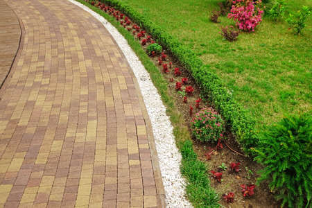 Modern Ornamental Garden Landscape With Tiled Colorful Mosaic Paving And Marble White Gravel Along Walkway