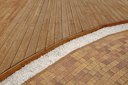 Backyard Dry Patio Or Terrace Surface In Perspective View. Composite Wood Decking, Drain System With White Marble Gravel And Stone Brick Paving