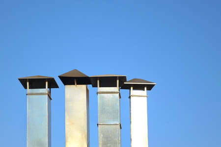 vent: Four Galvanized Chimney Pipe Or Vent Pipe In A Row On Blue Sky Background