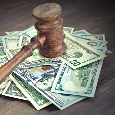 defendant: Stack Of Dollar Banknotes With Judges Or Auctioneers Gavel Or Hammer, Trial Or Tribunal Concept, Auction Concept, Close Up