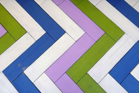 Decorated Artistic Wooden Multicolored Panel Background Or Texture With Parquet Herringbone Pattern. Colorful Wooden Wall. Rustic Vintage Modern Design.