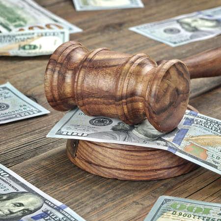Los jueces o subastadores mazo o martillo Y el dinero grande de la pila en el banco de madera o de fondo de madera, concepto para delitos financieros, de cerca
