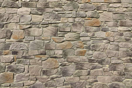 Modern Textured Grey Yellow Stonewall Made From Flagstone And Sandstone Slabs Background, Bumpy Stone Wall Texture, Rocky Structure Backdrop Stock Photo