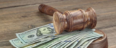 white collar crime: Judges or Auctioneers Gavel Or Hammer And Big Money Stack On Wooden Bench Or Wooden Table Background, Concept For Financial Crime, Close Up