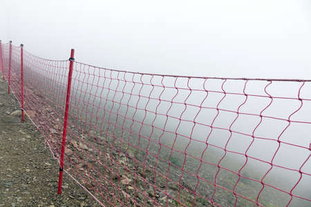 abyss: Rope Guard Fence From Red Netting Before Abyss In The Mountains In Foggy And Storm Weather On The Touristic Footpath Stock Photo