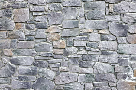 Modern Outdoor Building Stonewall Background Texture Decorated With Multicolored Split Face Natural Ledge Stone Tile In Medieval Style With Irregular And Chaotic Absrtact Mosaic Pattern, Close Up Stock Photo