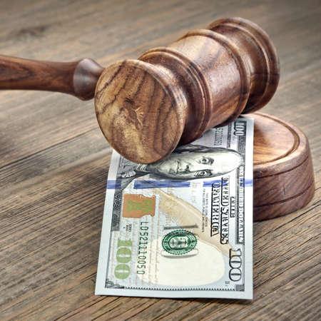 autoridad: Los jueces o subastadores mazo o martillo Y el dinero grande de la pila en el banco de madera o de fondo de madera, concepto para delitos financieros, de cerca