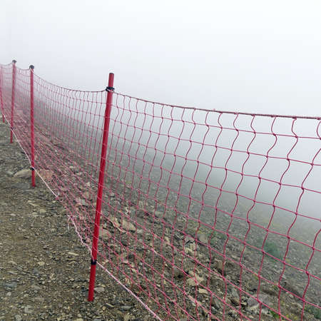 rockslide: Rope Guard Fence From Red Netting Before Abyss In The Mountains In Foggy And Storm Weather On The Touristic Footpath Stock Photo