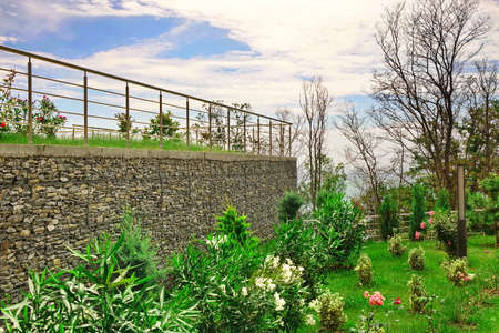 guardrails: Two Level Garden Terrace On The Hill Top With Stainless Steel Guardrails And Tropical Ornamental Garden With  Rocky Wall From Gabions