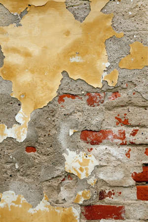 brickwall: Grunge Brickwall With Broken Stucco Vertical Texture. Old Brick Wall With Damaged Shabby Yellow Plaster Layer Background. Lime Wash Distressed Stonewall Wallpaper. Chipped Rough Uneven Stonewall Stock Photo