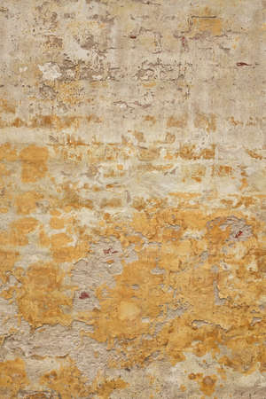 Grunge Brickwall With Broken Stucco Vertical Texture. Old Brick Wall With Damaged Shabby Yellow Plaster Layer Background. Lime Wash Distressed Stonewall Wallpaper. Chipped Rough Uneven Stonewall Reklamní fotografie