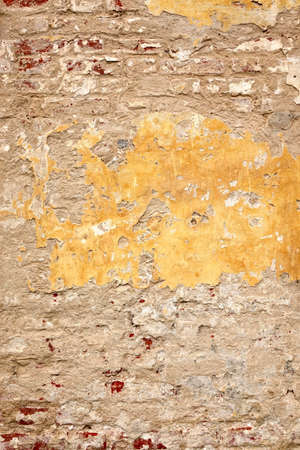 Grunge Brickwall With Broken Stucco Vertical Texture. Old Brick Wall With Damaged Shabby Yellow Plaster Layer Background. Lime Wash Distressed Stonewall Wallpaper. Chipped Rough Uneven Stonewall Stock Photo