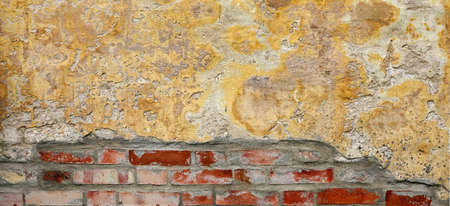 Grunge Brickwall With Broken Stucco Texture. Old Brick Wall With Damaged Shabby Yellow Plaster Layer Background. Lime Wash Distressed Stonewall Wallpaper. Chipped Rough Stonewall Uneven Web Banner