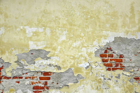 Old Brick Wall With Damaged Shabby Yellow Plaster Layer Background. Grunge Brickwall With Rundown Stucco Horizontal Texture. Lime Wash Distressed Vintage Stonewall Wallpaper. Chipped Stonewall Surface Reklamní fotografie