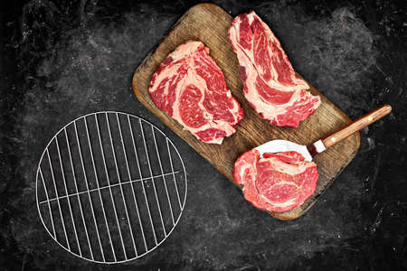 Raw Beef Steaks From Marbled Meet On Wooden Board And Empty Grill Steel Grate. Sirloin Beef Steaks, Overhead View. Three Raw Striploin Steaks from Marbled Beef on Black Background, Top View.