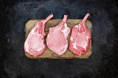 Raw Pork Bone Steaks On Brown Old Cutting Board. Tomahawk Pork Steaks On Chopping Board, Overhead View. Raw Three Pork Steaks On Wood Board And Black Background, Top View. 版權商用圖片