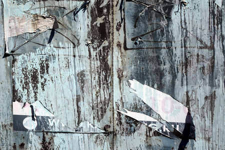 Old Billboard with Torn Posters. Dirty Street Wall with Crumpled, Wrinkled, Creased, Worn and Torn Posters. Abstract Vintage Background and Texture. 版權商用圖片