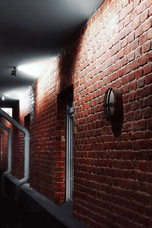Facade lighting On Brick Wall Of Old House At Night In Perspective View 版權商用圖片