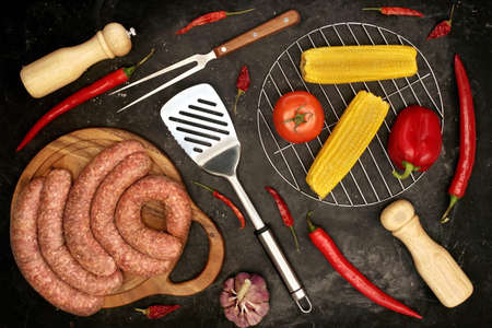 Raw Stuffed Sausages, Empty Grill, Vegetables, Grill Tools On Rough Black Background, Top View. Sausages in Natural Casing And Cookware. Sausages For Grilling or Frying On Black Table, Overhead View 版權商用圖片