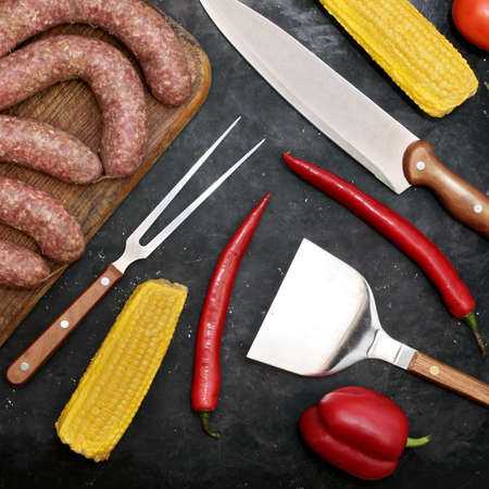 Sausages on Old Wooden Cutting Board, Vegetables and Grill Tools On Black Table Background, Top View. Raw Sausages in Natural Casing. Uncooked Stuffed Sausages For Grilling or Frying on Wood Board. 版權商用圖片