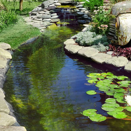Modern Landscaped Backyard Garden with Small Artificial Pond from PVC and Old Car as Designed Element. Modern Garden at House with Stony Landscaping Retro Style with Decorative Pond and Old Car. 版權商用圖片