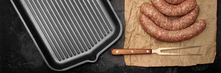 Raw Stuffed Sausages, Empty Grill Pan and Grill Tools On Rustic Black Table Background, Top View. Raw Sausages In Natural Casing. Sausages For Grilling or Frying On Paper Overhead View.