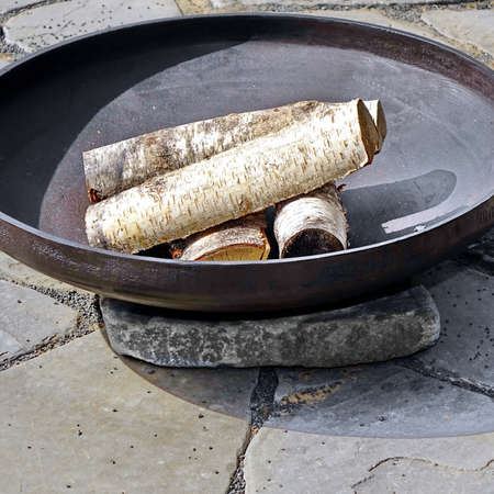 Patio Fire Pit Steel Round Table For Outdoor Leisure Party On The Stone Or Gravel Terrace. Iron Rounded Fire Pit With Grill Top On Backyard Party Place. Grill Appliance And Fireplace On The Back Yard 版權商用圖片