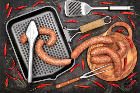 Raw Stuffed Sausages, Empty Grill Pan, Vegetables, Grill Tools On Rustic Black Background, Top View. Sausages in Natural Casing And Cookware. Sausages For Grilling or Frying On Paper, Overhead View