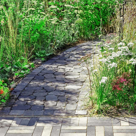 Back Yard Decorative Garden With Pathway Or Walkway From Black And Gray Cobblestone or Paving Stones. Back Yard Or Park With Stony Natural landscaping.