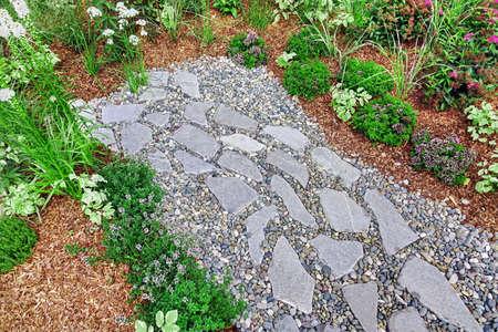 Backyard Garden Modern Designed Landscaping. Decorative Garden Design. Back Yard Lawn And Natural Mulched Border Between Grass, Plants And Pebble, Gravel Or Stone Walk Path. 版權商用圖片